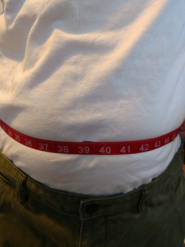 Measuring tape around a person wearing a tee shirt.